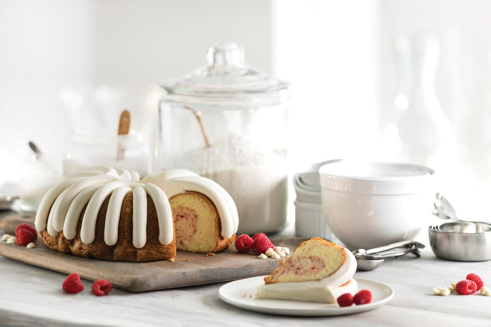A Bundt Cake with a slice cut out of it, surrounded with fresh raspberries
