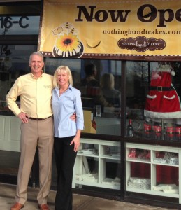 Image of a couple in front of a nothing bundt cakes banner