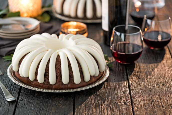 Chocolate Bundt Cake on a wooden table with a wine bottle and glasses of red wine.