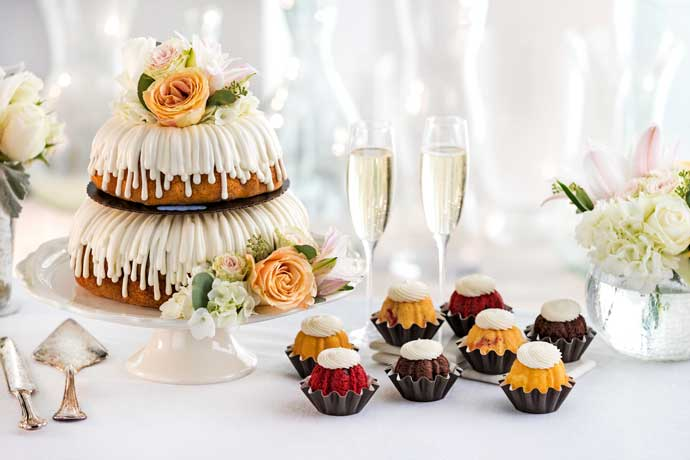 Tiered Bundt Cake decorated with white and yellow roses, with bundtinis and champagne flutes.