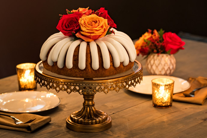 Bundt Cake on a pedestal with red and orange roses