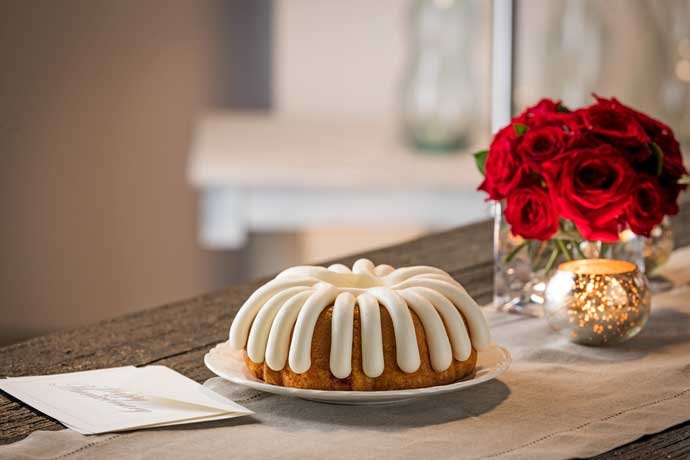 Bundt Cake on a wooden table with a white table runner, next to red roses and a card envelope